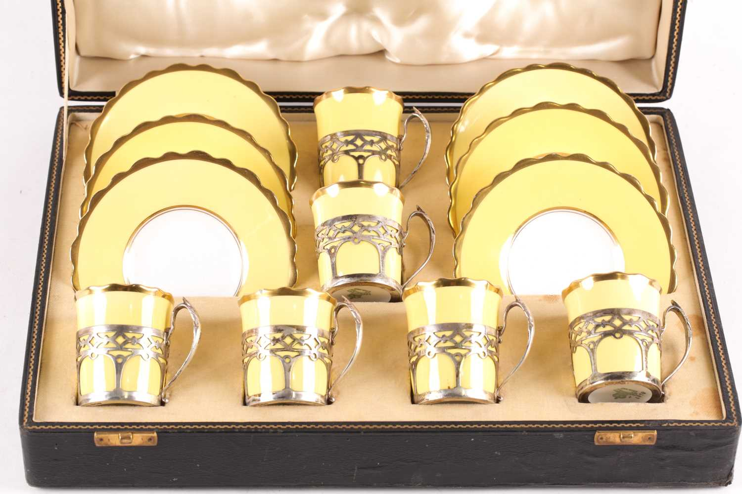 A set of six Aynsley bone china silver-mounted coffee cans and saucers, the two-tone yellow and
