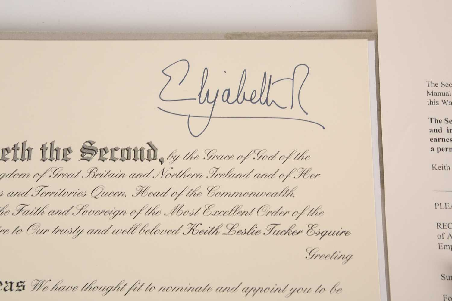 An M.B.E certificate to Keith Leslie Tucker (M.B.E) signed (printed signatures) by her majesty Queen - Image 7 of 10