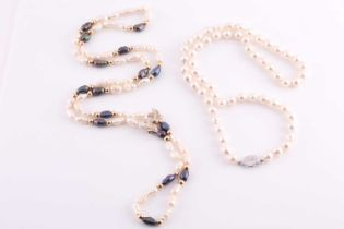A white and black 'rice krispie' pearl necklace, fastened with a small yellow metal bow-shaped