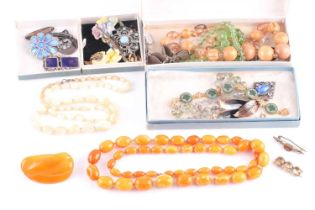 A small group of costume jewellery items to include an amber style (plastic) necklace, three