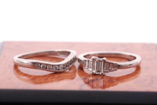 A platinum and diamond ring, set with an emerald-cut diamond of approximately 0.32 carats, the