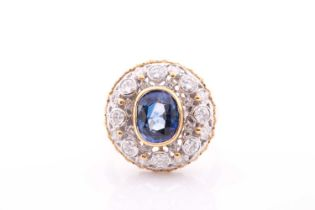 An unusual diamond and sapphire cluster ring, of bombe design, centred with a mixed oval-cut