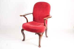 A George II style walnut library armchair with stuff over upholstery and shaped broad crook arms