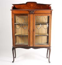 An early 20th century inlaid mahogany display cabinet. With a pair of leaded glazed doors on