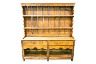 A 19th century stripped pine two drawer pot board dresser and rack, with shaped apron and square