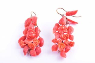 A pair of yellow metal and carved coral drop earrings, wire-set with foliate and floral carved red