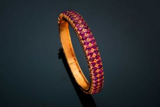 A ruby bangle; composed of two rows of mixed oval cut rubies in carved claw mounts to a foliate