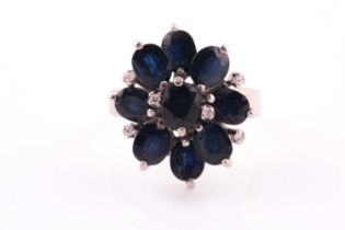 A 1970's sapphire and diamond cluster ring, the nine oval mixed cut sapphires set with six diamond