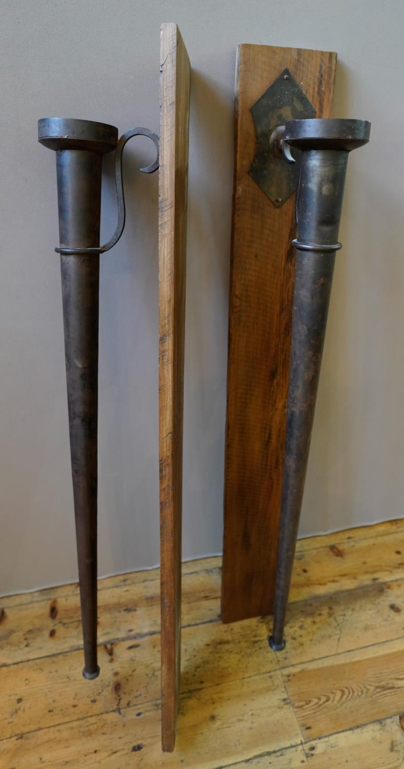 A PAIR OF LARGE WALL MOUNTED TAPERED CYLINDRICAL METAL CANDLE HOLDERS, with serpentine brackets moun