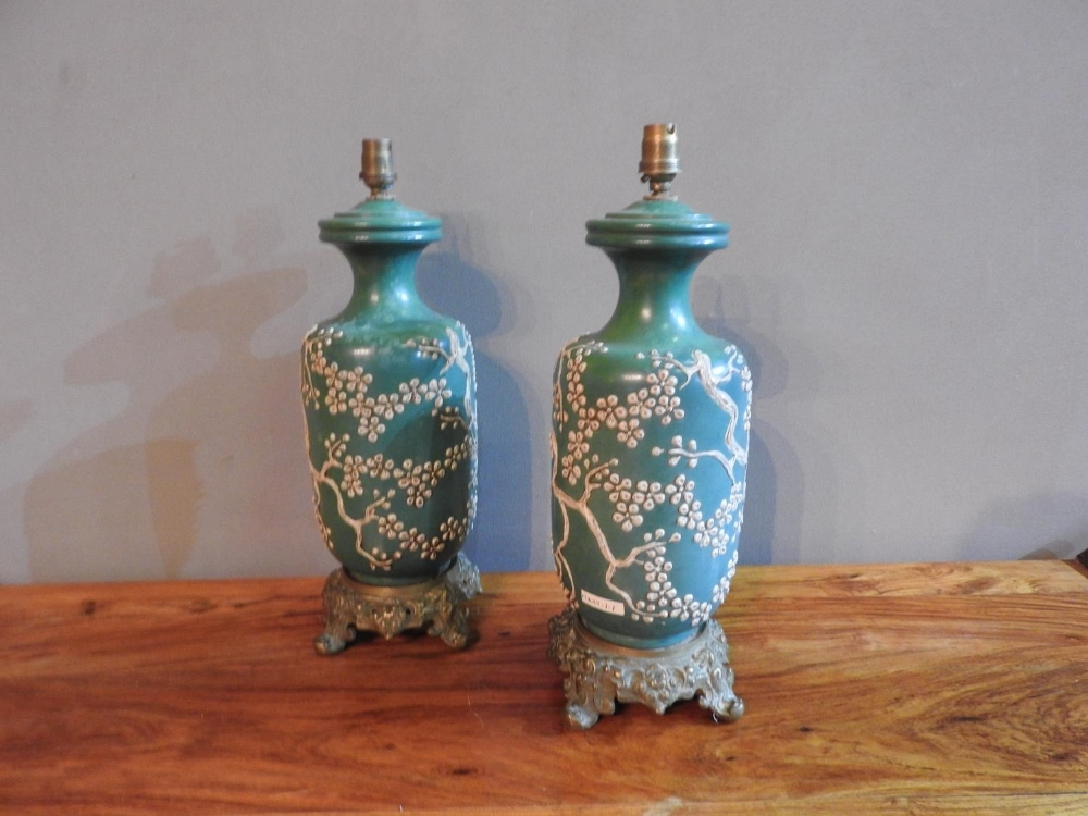 A PAIR OF 19th CENTURY CHINESE GREEN GLAZED TABLE LAMPS EMBOSSED WITH BLOSSOM PATTERN ON ORNATE BRAS