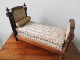 LOUIS XVI STYLE WALNUT AND UPHOLSTERED TOY BED LATE 19TH CENTURY covered in pink striped silk fabric