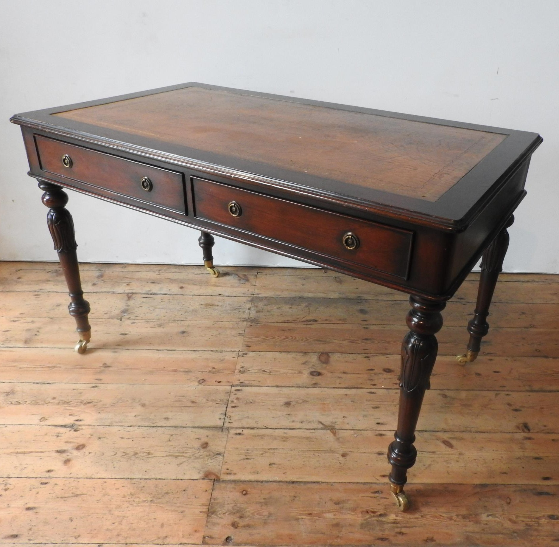 A 20TH CENTURY MAHOGANY REGENCY STYLE LIBRARY TABLE, with leather top, the legs carved with tulip