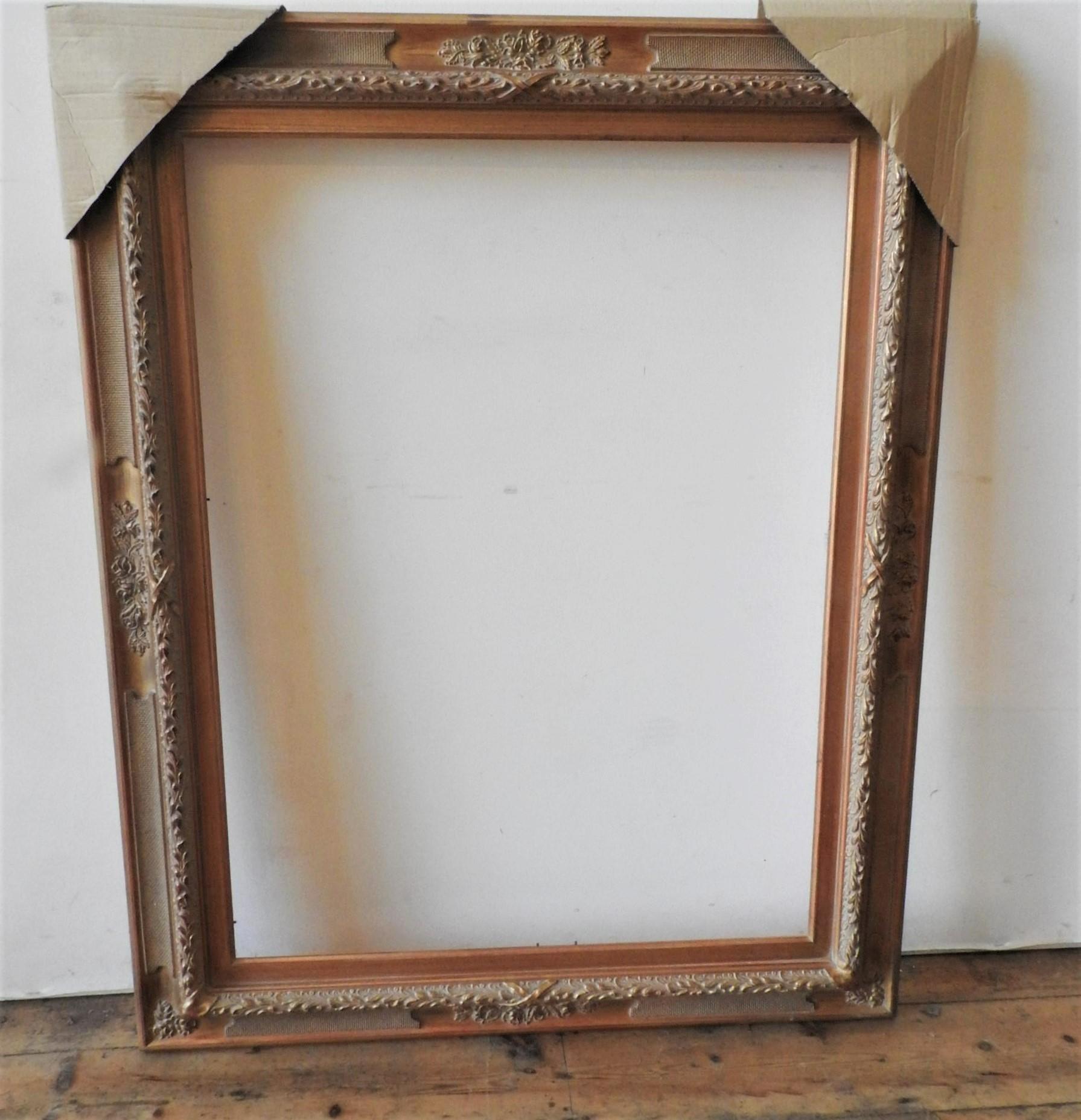 A CONTEMPORARY FOLIATE DECORATED GILT PICTURE FRAME, 129 x 101 cm