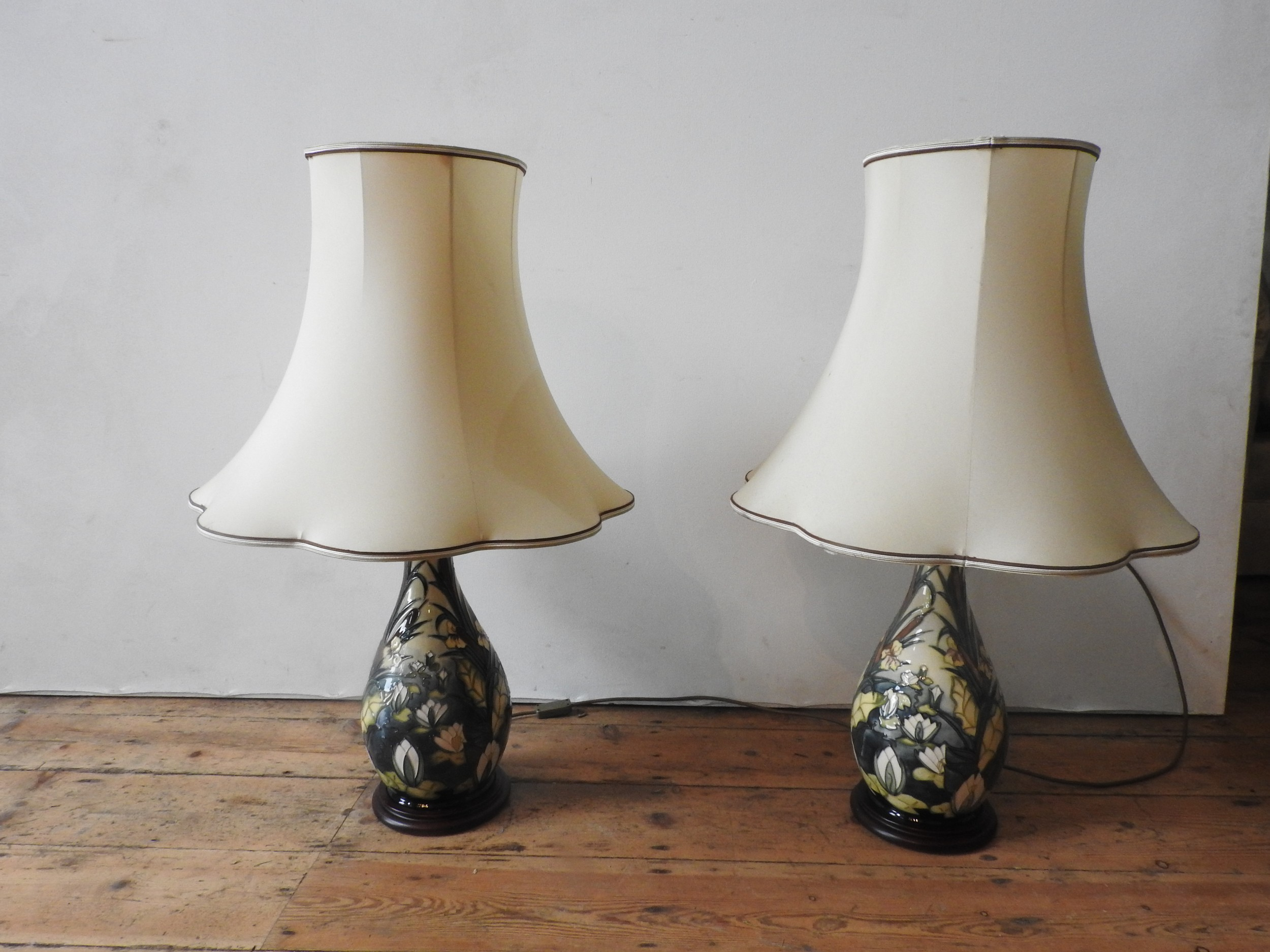 A PAIR OF CREAM GLAZED MOORCROFT TABLE LAMPS, decorated with lillies and bull rushes, both