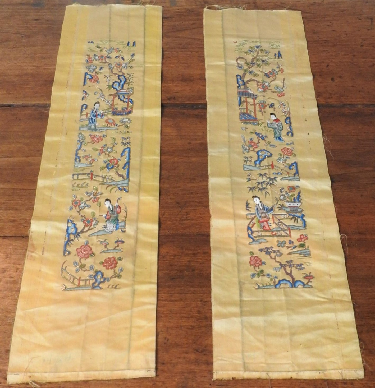 TWO GOLD COLOURED EMBROIDERED ORIENTAL SILK PANELS depicting geishas in pleasure garden, 70 x 19