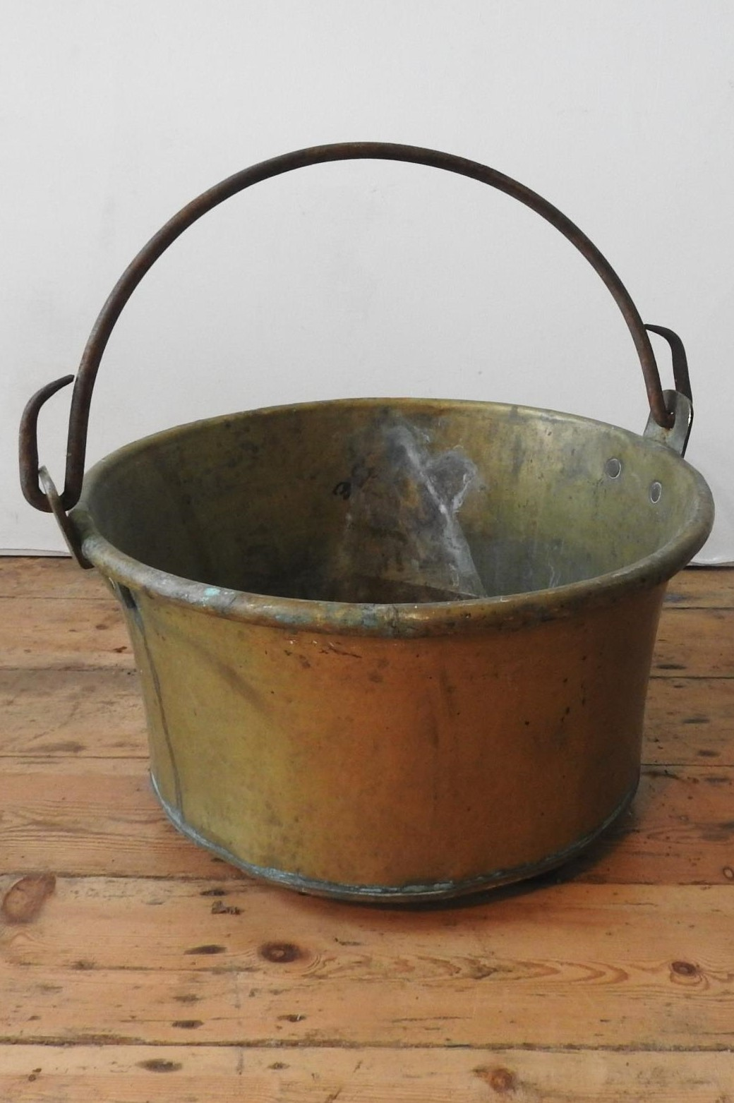 A CONTINENTAL RIVETED BRASS BUCKET WITH IRON RING HANDLE, 52cm dia