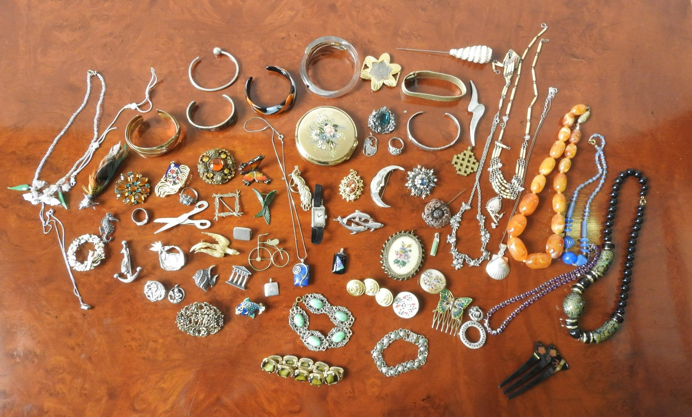 A QUANTITY OF COSTUME JEWELLERY BROOCHES, NECKLACES BRACELETS AND COMPACT