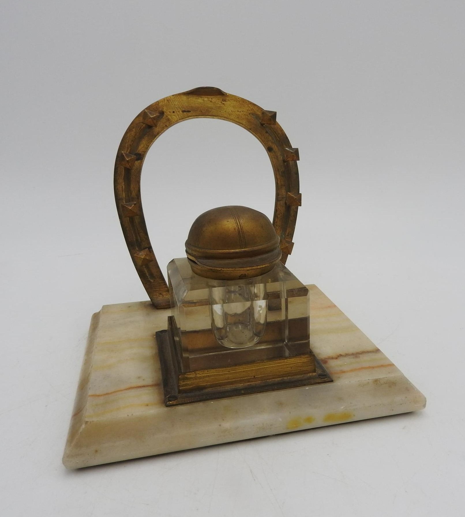 A NOVELTY JOCKEY'S INKWELL STAND, comprising of a horseshoe shaped pen rack and an inkwell with a