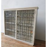 A CREAM PAINTED LEADED LIGHT TWO DOOR BOOKCASE, with three interior shelves, 113 x 126 x 24cm