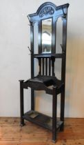 AN OAK ART NOUVEAU HALL STAND WITH MIRRORED BACK PANEL, hammered cast-metal coat hooks, the top