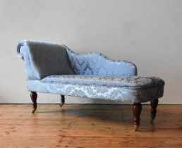 A CHILD'S DAMASK UPHOLSTERED CHAISE LONGUE, covered in teal blue fabric with embroidered foliate