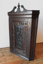 A CONTINENTAL OAK 19TH CENTURY ORNATE CARVED CORNER CUPBOARD, with scroll and finial pediment and