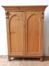 A 19TH CENTURY WAXED PINE ARCH PANELLED CUPBOARD, with cornice, bookcase stands on an oak base,