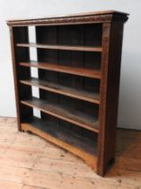 A 19TH CENTURY CARVED OAK 5-TIER ADJUSTABLE BOOKSHELF, wth a foliate carved frieze and side