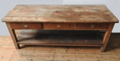 A RUSTIC PINE FARMHOUSE PLANK TOP DRESSER BASE, with three drawers and shelf below, 73 x 69 x 190 cm