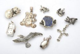 A collection of silver coloured charms and brooches