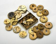 A collection of watch movements, dust covers and parts