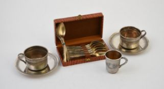 A pair of French silver coloured cups and saucers