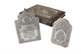 A silver coloured mounted Quran