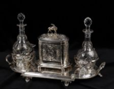 An early 20th century silver plated decanter and biscuit box stand