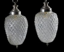 A pair of modern chrome and glass ceiling lights