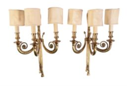 A pair of gilt metal three branch wall lights in Louis XVI style