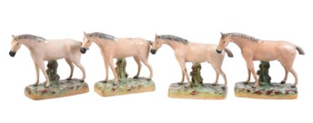 A group of similar Staffordshire pottery models of four dun horses of William Kent Ltd. type