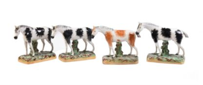 A group of similar Staffordshire pottery models of three piebald horses and one skewbald horse