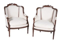 A pair of French carved mahogany armchairs in Louis XVI style