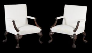 A pair of carved mahogany armchairs in George II style