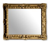 A CARVED GILTWOOD AND COMPOSITION WALL MIRROR