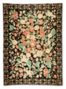 A WOOL CARPET WITH PERFUSE SUMMER FLOWERS ON A DARK BLUE GROUND