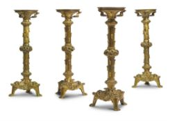 A SET OF FOUR GILT BRASS GOTHIC REVIVAL CANDLESTICKS, FRENCH OR ENGLISH