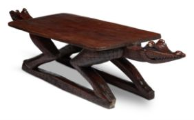 A LARGE HARDWOOD LOW TABLE MODELLED AS ADORSED CROCODILES