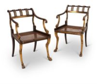 A PAIR OF REGENCY FAUX ROSEWOOD AND PARCEL GILT ARMCHAIRS