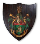 A STAINED PINE PAINTED ARMORIAL PANEL, OF CARTOUCHE SHAPE