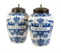 A pair of Dutch Delft blue and white tobacco jars and brass covers