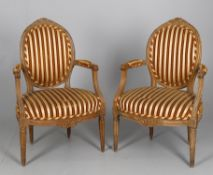 A pair of beech and upholstered fauteuils