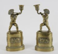 A pair of early 19th century French brass candlesticks