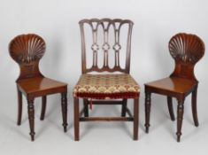 A pair of early Victorian mahogany shell back hall chairs
